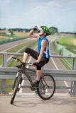 Biker drinking isotonic drink and having rest. Mountain biker drinking isotonic drink and having rest over highway Royalty Free Stock Images