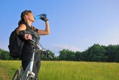 Biker drinking water. Pretty biker drinking water during the brake in green environment Stock Photo