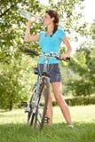 Biker drinking water. Young woman biker thirsty drinking water Stock Photo