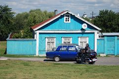 A biker drives a motorbike by an old wooden house. Royalty Free Stock Images