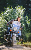 Biker driving his cruiser motorcycle on road in the forest. Biker with beard driving his cruiser motorcycle in the forest. Man is wearing leather jacket and blue Royalty Free Stock Photography