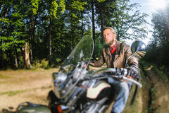 Biker driving his cruiser motorcycle on road in the forest. Biker with beard driving his cruiser motorcycle in the forest. Man is wearing leather jacket and blue Royalty Free Stock Photo