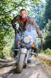 Biker driving his cruiser motorcycle on road in the forest. Concentrated biker with beard driving his cruiser motorcycle in the forest. Man is wearing leather Royalty Free Stock Images