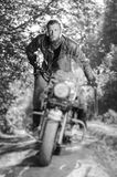 Biker driving his cruiser motorcycle on road in the forest. Concentrated biker with beard driving his cruiser motorcycle in the forest. Man is wearing leather Stock Photos