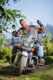 Biker driving his cruiser motorcycle on road in the forest. Handsome biker with beard driving his cruiser motorcycle in the forest and giving the devil horns Stock Photos