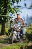 Biker driving his cruiser motorcycle on road in the forest. Handsome biker with beard driving his cruiser motorcycle in the forest and looking aheat. Man is Royalty Free Stock Image