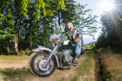 Biker driving his cruiser motorcycle on road in the forest. Handsome biker with beard driving his cruiser motorcycle in the forest. Man is wearing leather jacket Stock Photography