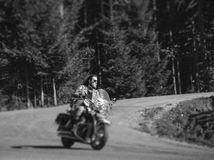 Biker driving his cruiser motorcycle on road in the forest. Handsome biker with beard driving his cruiser motorcycle by nice road in the forest. Man is wearing Royalty Free Stock Photo