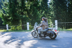 Biker driving his cruiser motorcycle on road in the forest. Man with beard driving his cruiser motorcycle by nice road in the forest. Man is wearing leather Stock Photography