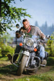 Biker driving his cruiser motorcycle on road in the forest. Serious biker with beard driving his cruiser motorcycle in the forest. Man is wearing leather jacket Royalty Free Stock Photos