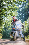 Biker driving his cruiser motorcycle on road in the forest. Serious biker with beard driving his cruiser motorcycle in the forest. Man is wearing leather jacket Stock Image