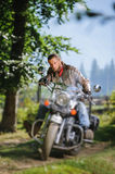 Biker driving his cruiser motorcycle on road in the forest. Serious man with beard driving his cruiser motorcycle in the forest. Man is wearing leather jacket Royalty Free Stock Images