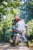 Biker driving his cruiser motorcycle on road in the forest. Serious man with beard driving his cruiser motorcycle in the forest. Man is wearing leather jacket Royalty Free Stock Photos
