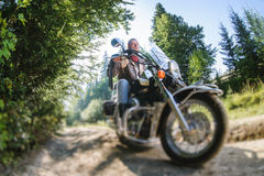 Biker driving his cruiser motorcycle on road in the forest. Young biker with beard driving his cruiser motorcycle in the forest. Man is wearing leather jacket Stock Photos