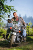 Biker driving his cruiser motorcycle on road in the forest. Young biker with beard driving his cruiser motorcycle in the forest and smilling. Man is wearing Royalty Free Stock Photo
