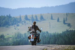 Biker driving his cruiser motorcycle on road Royalty Free Stock Image