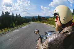 Biker driving his motorcycle on the open road. Young man biker driving fast on the open road in the mountains, wearing leather jacket and helmet. Shot from the Royalty Free Stock Photography