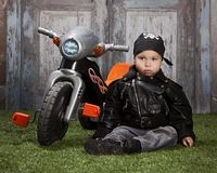 Biker Dude. Adorable toddler dressed in a bandanna and leather jacket and sitting next to a toy tricycle Royalty Free Stock Image