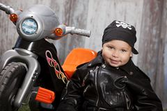 Biker Dude. Adorable toddler dressed in a bandanna and leather jacket and sitting next to a toy tricycle Stock Images