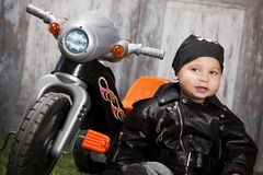 Biker Dude. Adorable toddler dressed in a bandanna and leather jacket and sitting next to a toy tricycle Royalty Free Stock Images