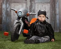 Biker Dude. Adorable toddler dressed in a bandanna and leather jacket and sitting next to a toy tricycle Royalty Free Stock Photo