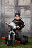 Biker Dude. Adorable toddler dressed in a bandanna and leather jacket and sitting next to a toy tricycle Stock Image