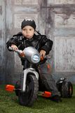 Biker Dude. Adorable toddler dressed in a bandanna and leather jacket and sitting on a toy tricycle Stock Images