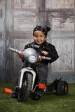 Biker Dude. Adorable toddler dressed in a bandanna and leather jacket and sitting on a toy tricycle Stock Image