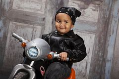 Biker Dude. Adorable toddler dressed in a bandanna and leather jacket and sitting on a toy tricycle Royalty Free Stock Images