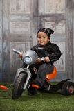 Biker Dude. Adorable toddler dressed in a bandanna and leather jacket and sitting on a toy tricycle Royalty Free Stock Photos