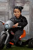 Biker Dude. Adorable toddler dressed in a bandanna and leather jacket and sitting on a toy tricycle Royalty Free Stock Image