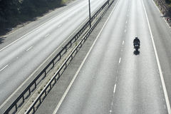 Biker On An Empty Highway Stock Photos
