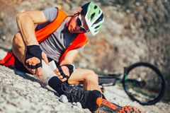 The biker fell from a bike, using a bandage from his first aid kit to help himself. Bicycle accident royalty free stock image