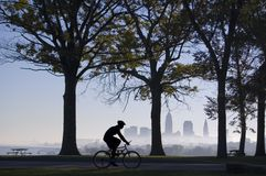 Biker on Foggy Morning. Silhouette of biker riding in park with trees and Cleveland skyline in background on a foggy morning Royalty Free Stock Images