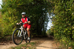 Biker on the forest road riding outdoor Royalty Free Stock Image