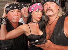 Biker Gang with Beautiful Woman. Three motorcycle gang members with beautiful women in leather Stock Photo