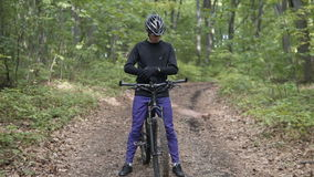 Biker Get Ready for Ride. Closeup shot of young sports man, wears black helmet and yellow glasses, starts to ride bicycle on the tree forest stock video footage