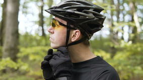 Biker Get Ready for Ride. Closeup shot of young sports man, wears black helmet and yellow glasses, starts to ride bicycle on the tree forest stock video