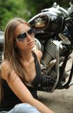 Biker girl. Sitting next to a bike Royalty Free Stock Photos