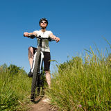 Biker girl. Young girl riding a bike on a field path - offroad biker in a sunny day Stock Images