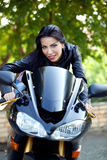 Biker girl. Attractive girl riding a bike royalty free stock photography