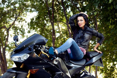 Biker girl. Beautiful biker girl and power motorcycle royalty free stock image