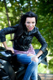 Biker girl. Beautiful angry biker girl and power motorcycle royalty free stock images