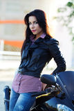 Biker girl. Attractive girl stands near a bike royalty free stock photography
