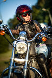 Biker girl. Sits on a motorcycle Stock Photography