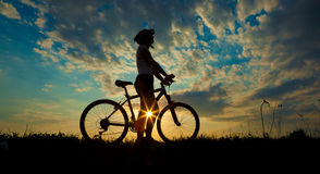 Biker-girl. At the sunset on the meadow Stock Photography