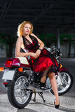 Biker girl in dress on a motorcycle over the Stock Photography