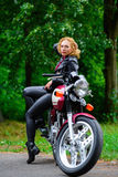 Biker girl in leather jacket on a motorcycle Stock Photo