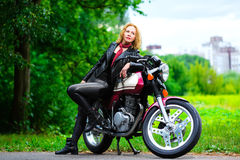 Biker girl in leather jacket on a motorcycle Stock Photography
