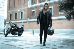Biker girl in a leather jacket on a motorcycle Stock Photography